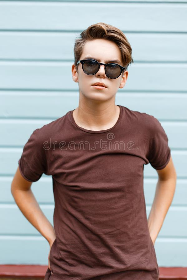 Fashionable modern young hipster man in dark sunglasses in trendy summer t-shirt with stylish hairstyle stands. Near the vintage blue wooden wall. Handsome guy stock photo