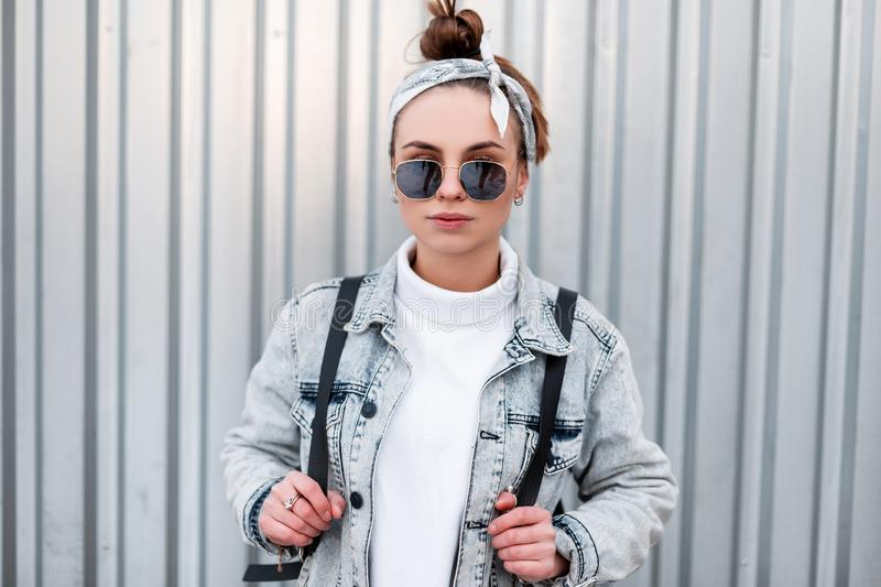 Fashionable modern young woman hipster in a bandana with a stylish hairstyle in a denim jacket in trendy sunglasses stock images