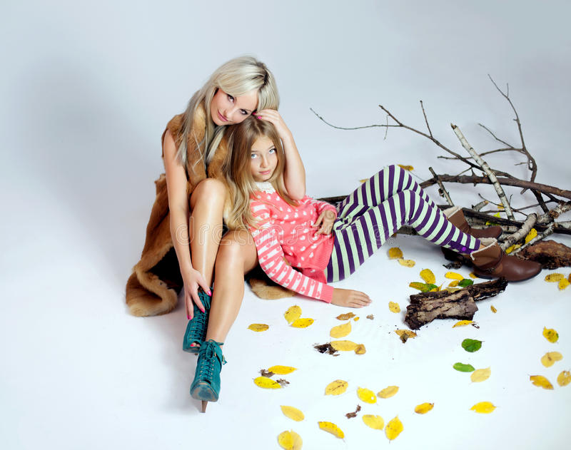 Fashionable mother with daughter. Beautiful mother posing with daughter in studio. Fashion photo.Winter style stock photos