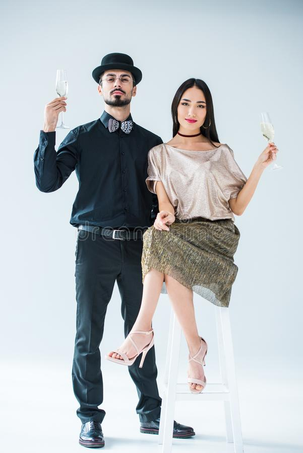 Fashionable multicultural couple with glasses of champagne looking at camera. Isolated on white stock images