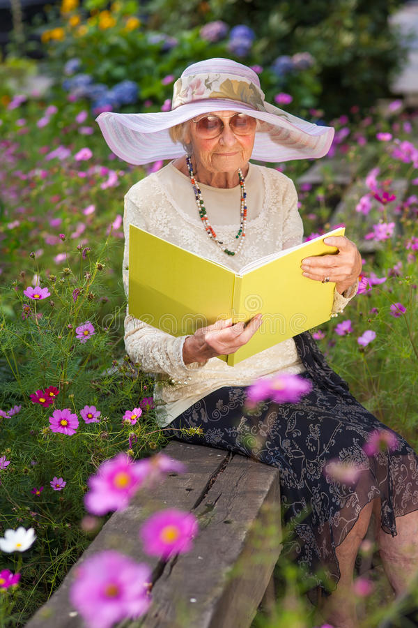 Fashionable Old Lady Reading In Her Garden Stock Photo