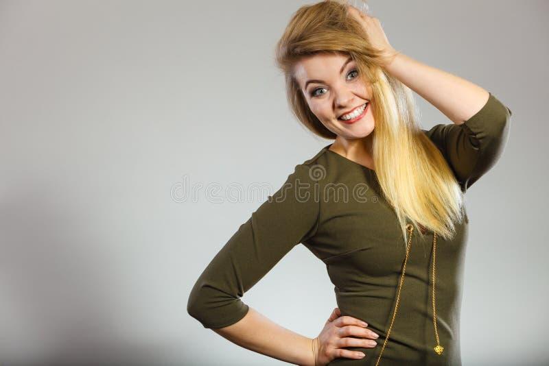 Attractive blonde woman wearing tight green khaki dress stock photo
