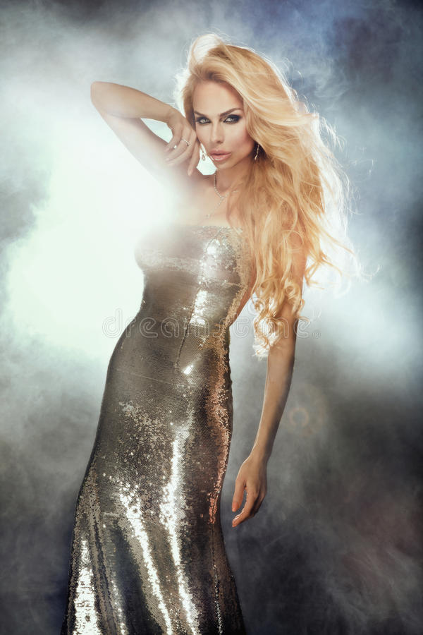 Portrait of cute blonde woman wearing silver fashionable dress. royalty free stock photography