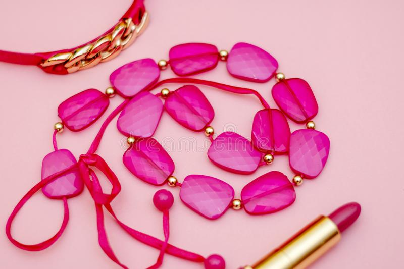 Fashionable pink accessories - beads, lipstick, belt on a gentle pink background. flay lay. stock image