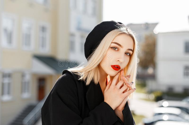 Fashionable portrait of a beautiful blonde woman in a black coat. And a black beret on a sunny day stock photos