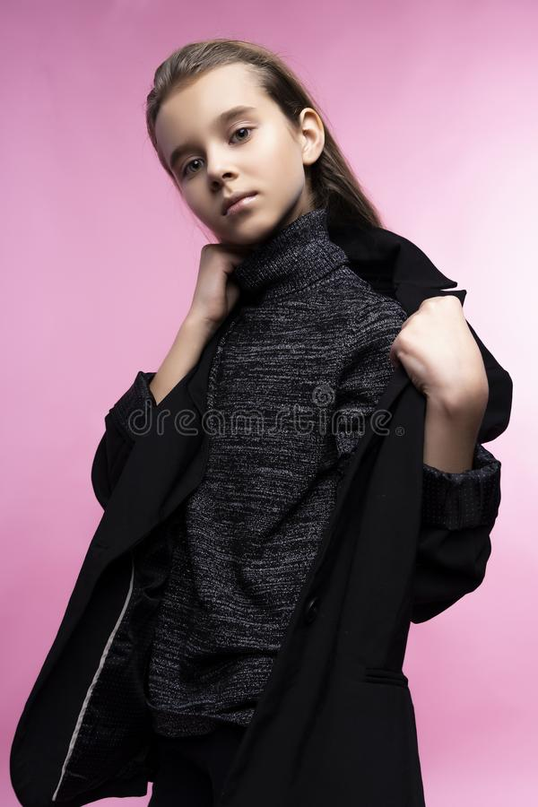 Fashionable portrait of beautiful cute teen girl wearing a gray turtleneck, jeans and blazer jacket. Pink background. Advertising stock image