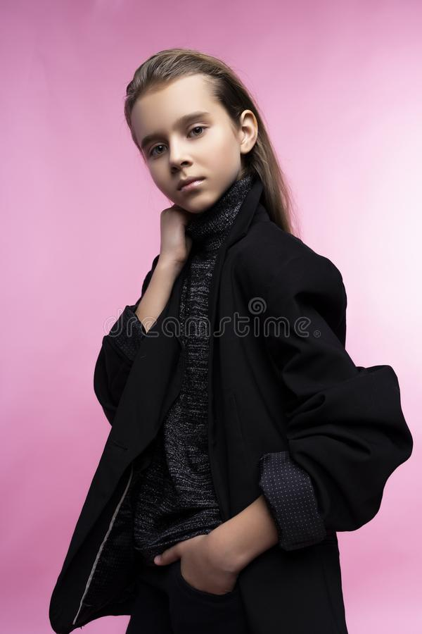 Fashionable portrait of beautiful cute teen girl wearing a gray turtleneck, jeans and blazer jacket. Pink background. Advertising royalty free stock image