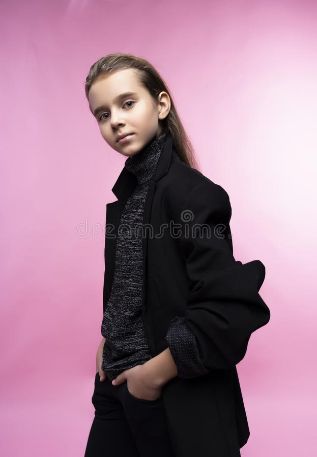 Fashionable portrait of beautiful cute teen girl wearing a gray turtleneck, jeans and blazer jacket. Pink background. Advertising stock photos