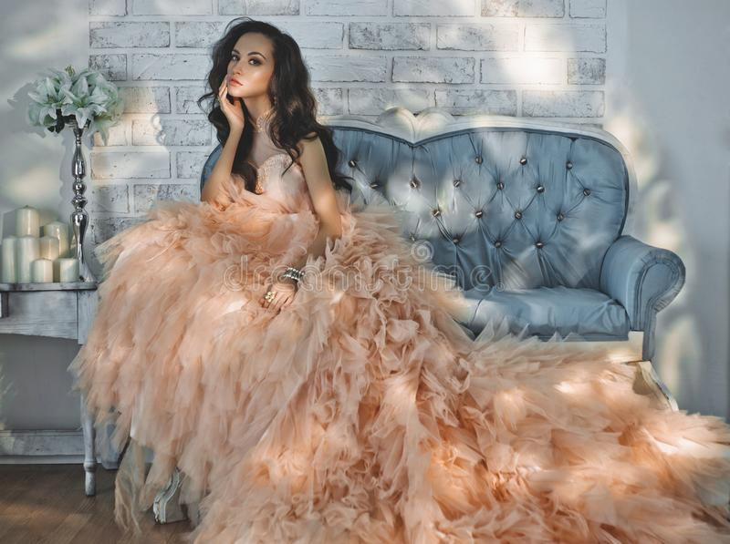 Beautiful lady in gorgeous couture dress on sofa. Fashionable portrait of beautiful lady in gorgeous couture dress on sofa. Holidays & Events. Evening dress royalty free stock photos