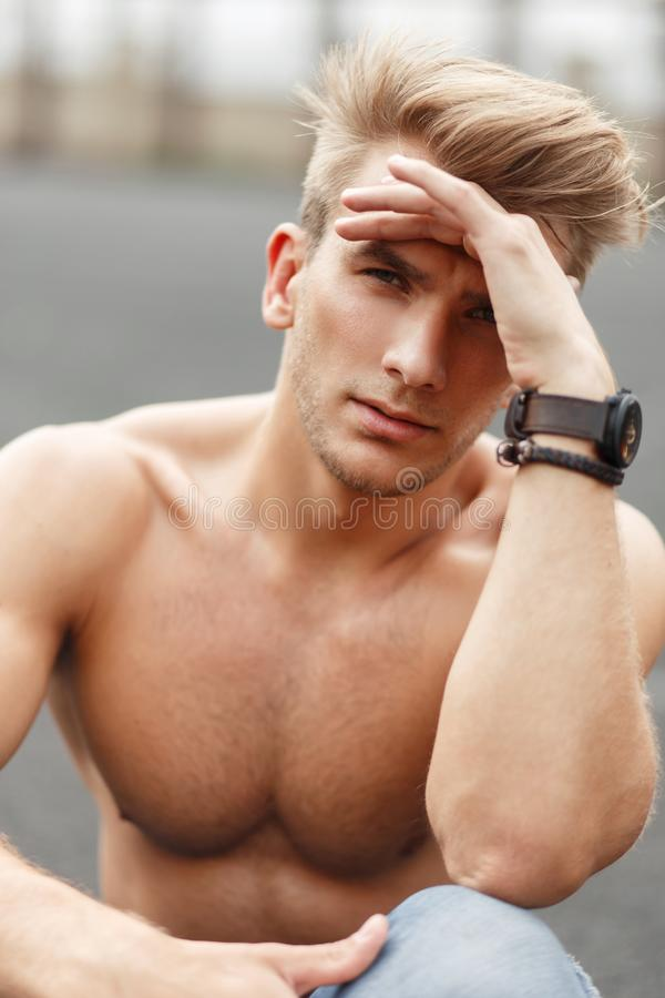 Fashionable portrait of a beautiful sporty model man with a hair. Style with a healthy body sitting on the street stock photography