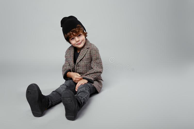 Fashionable portrait of a cute boy seated down in studio, wearing fashionable, looking,  on a white background royalty free stock photo