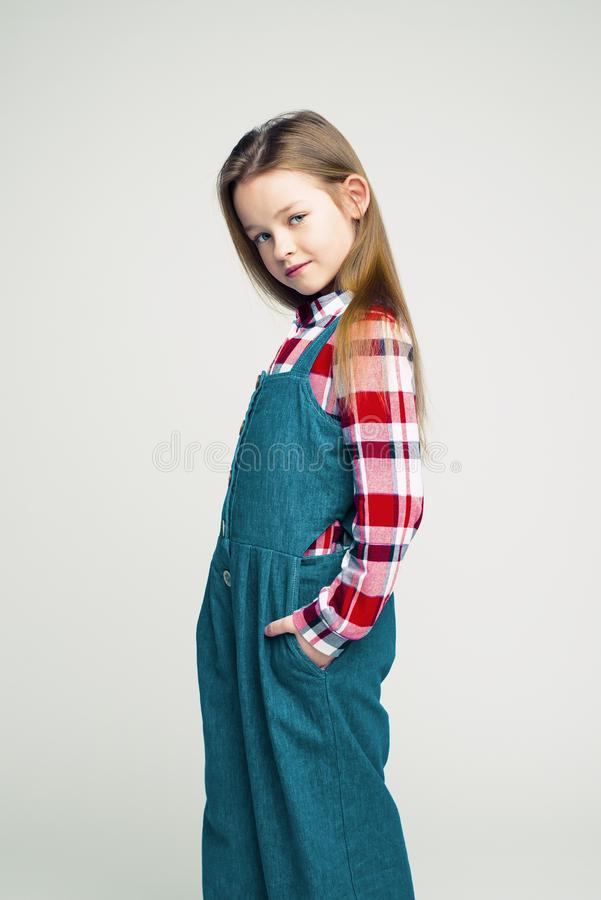 Fashionable portrait of a little girl in a denim jumpsuit and a plaid shirt. children`s studio shooting stock photos
