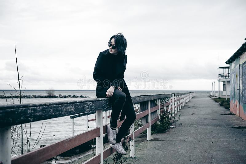 Emotional fashionable portrait of a young brunette woman in black clothes, jeans T-shirt, coat and sunglasses, in a Gothic style s. Fashionable portrait of a stock photography