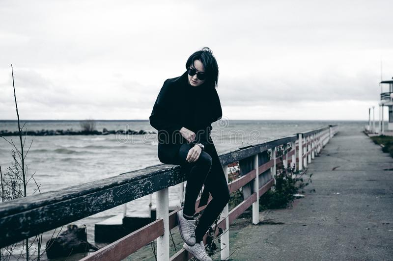 Emotional fashionable portrait of a young brunette woman in black clothes, jeans T-shirt, coat and sunglasses, in a Gothic style s. Fashionable portrait of a stock photos