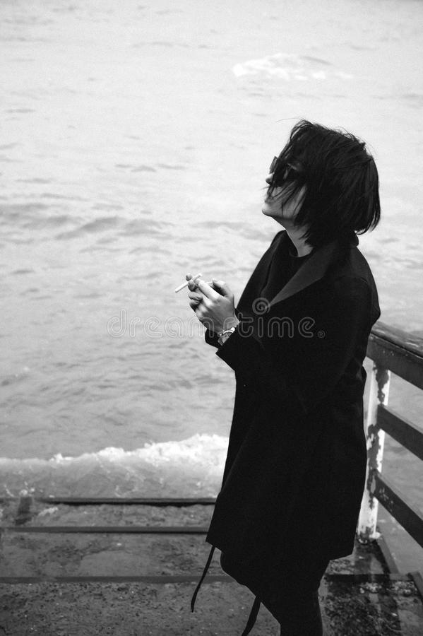 Emotional fashionable portrait of a young brunette woman in black clothes, jeans T-shirt, coat and sunglasses, in a Gothic style s. Fashionable portrait of a royalty free stock photo