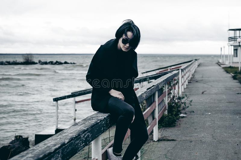 Emotional fashionable portrait of a young brunette woman in black clothes, jeans T-shirt, coat and sunglasses, in a Gothic style s. Fashionable portrait of a royalty free stock photography