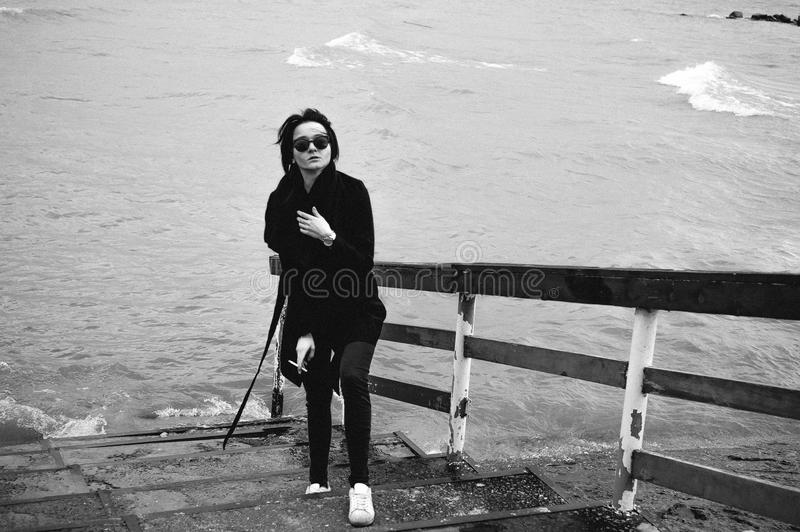 Emotional fashionable portrait of a young brunette woman in black clothes, jeans T-shirt, coat and sunglasses, in a Gothic style s. Fashionable portrait of a royalty free stock images