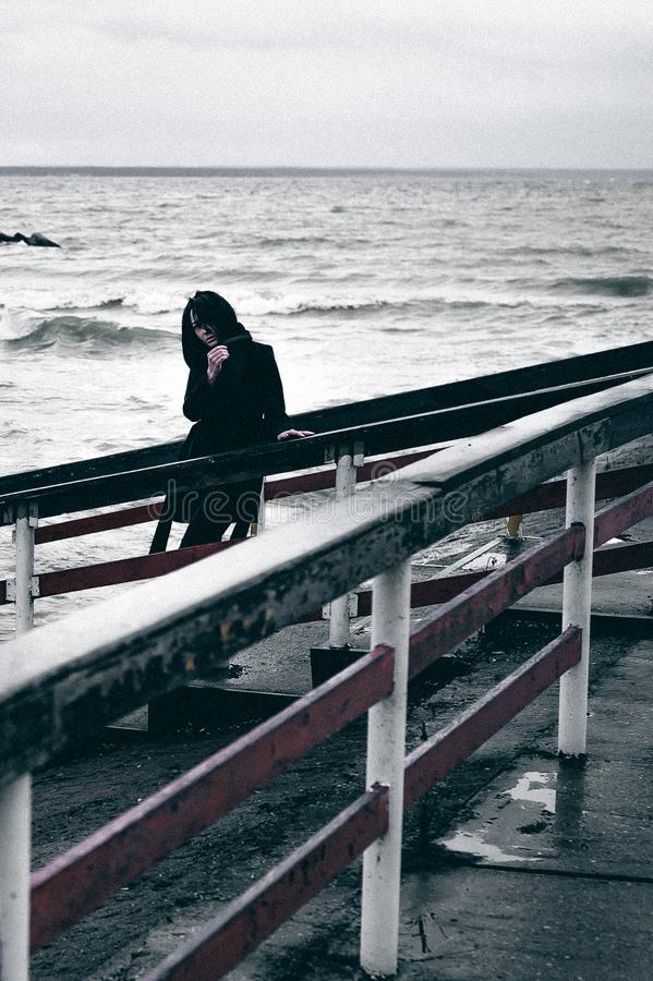 Fashionable portrait of a young brunette woman in black clothes, jeans T-shirt, coat and sunglasses, in a Gothic style sad mood. o. N an empty beach, on an stock image