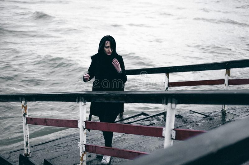 Emotional fashionable portrait of a young brunette woman in black clothes, jeans T-shirt, coat and sunglasses, in a Gothic style s. Fashionable portrait of a royalty free stock photos