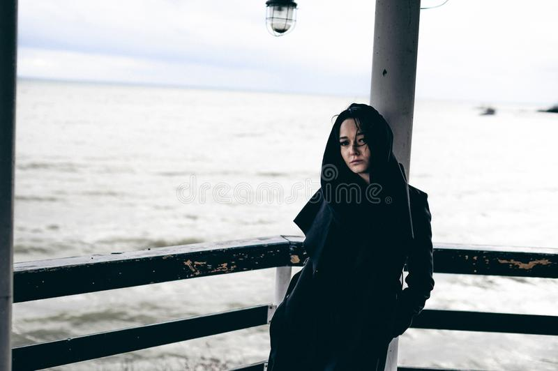 Emotional fashionable portrait of a young brunette woman in black clothes, jeans T-shirt, coat and sunglasses, in a Gothic style s. Fashionable portrait of a royalty free stock image
