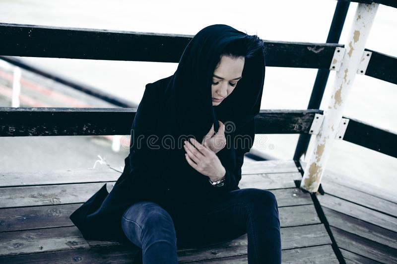 Fashionable portrait of a young brunette woman in black clothes, jeans T-shirt, coat and sunglasses, in a Gothic style sad mood. On an empty beach, on an stock photography