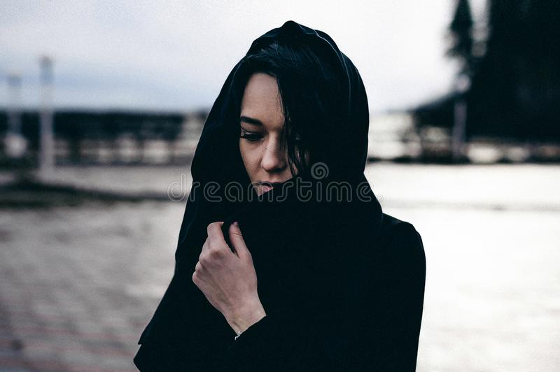 Fashionable portrait of a young brunette woman in black clothes, jeans T-shirt, coat and sunglasses, in a Gothic style sad mood. On an empty beach, on an royalty free stock photos