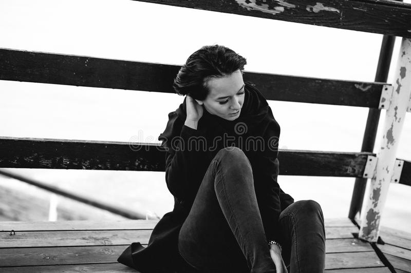 Fashionable portrait of a young brunette woman in black clothes, jeans T-shirt, coat and sunglasses, in a Gothic style sad mood. On an empty beach, on an royalty free stock photography