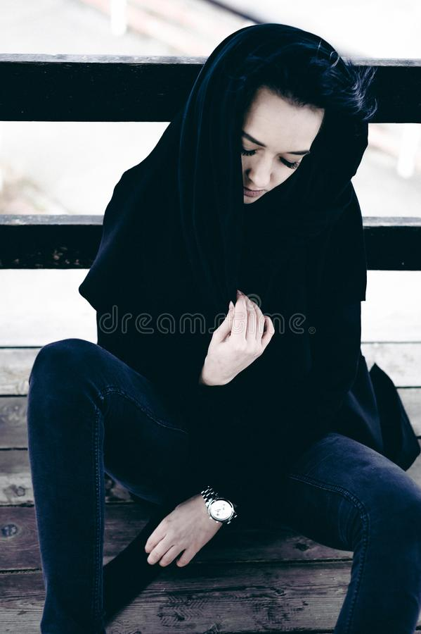 Fashionable portrait of a young brunette woman in black clothes, jeans T-shirt, coat and sunglasses, in a Gothic style sad mood. On an empty beach, on an stock images