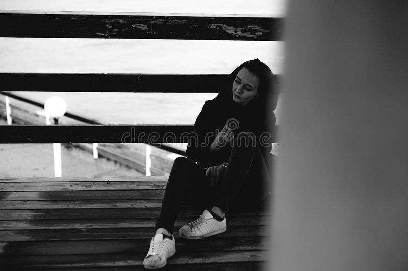 Fashionable portrait of a young brunette woman in black clothes, jeans T-shirt, coat and sunglasses, in a Gothic style sad mood. On an empty beach, on an stock image