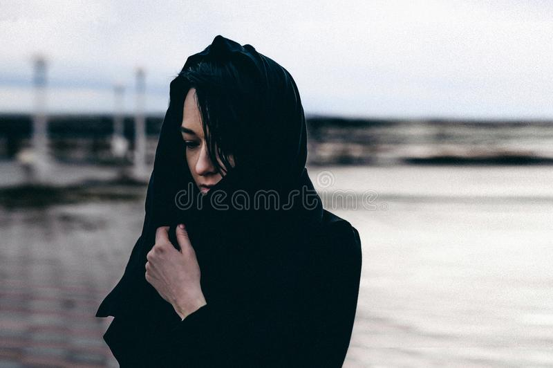 Fashionable portrait of a young brunette woman in black clothes, jeans T-shirt, coat and sunglasses, in a Gothic style sad mood. On an empty beach, on an royalty free stock photo