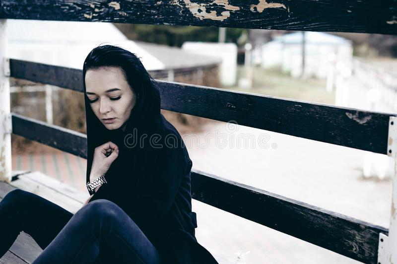 Fashionable portrait of a young brunette woman in black clothes, jeans T-shirt, coat and sunglasses, in a Gothic style sad mood. On an empty beach, on an royalty free stock image