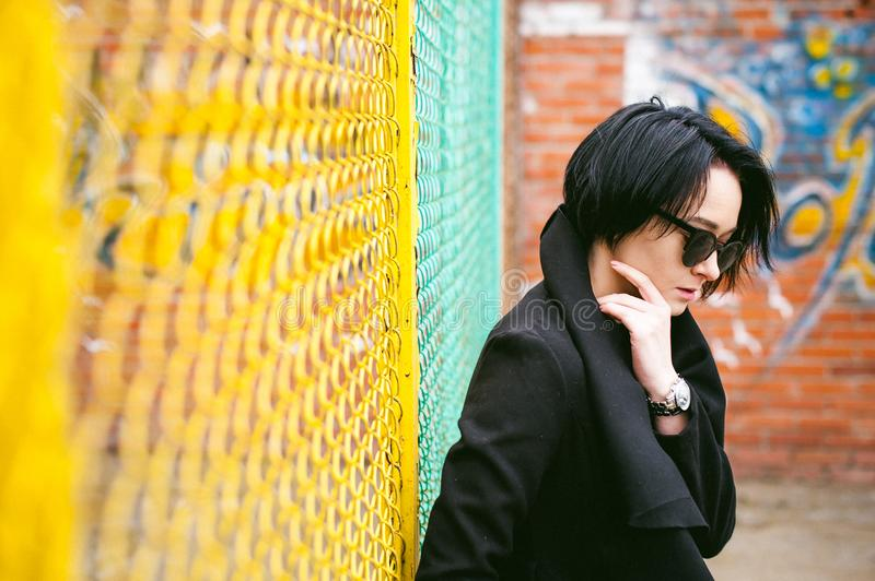 Fashionable portrait of a young brunette woman in black clothes, jeans T-shirt, coat and sunglasses, in a Gothic style sad mood. o. Emotional fashionable stock photography