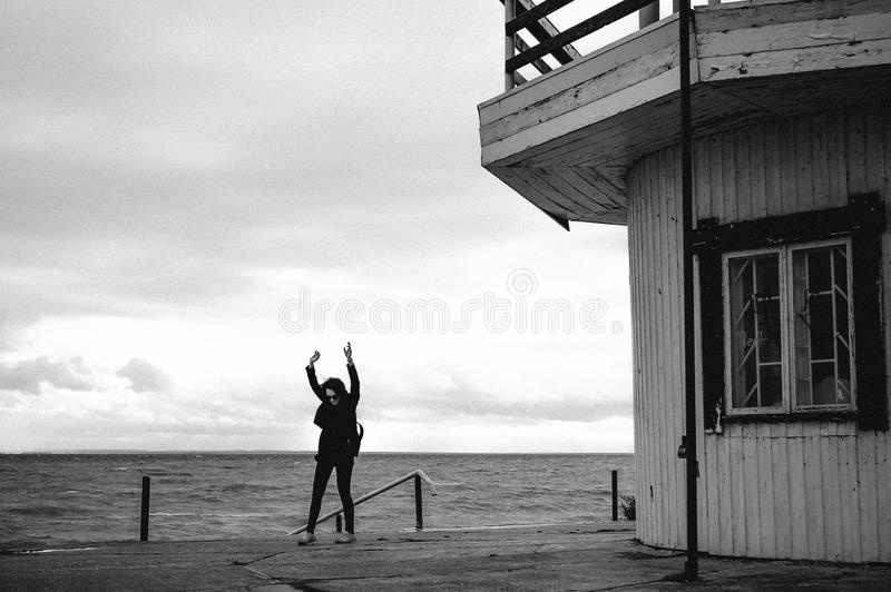 Fashionable portrait of a young brunette woman in black clothes, jeans T-shirt, coat and sunglasses, in a Gothic style sad mood. o. N an empty beach, on an stock photos