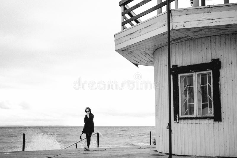 Fashionable portrait of a young brunette woman in black clothes, jeans T-shirt, coat and sunglasses, in a Gothic style sad mood. o. N an empty beach, on an royalty free stock image