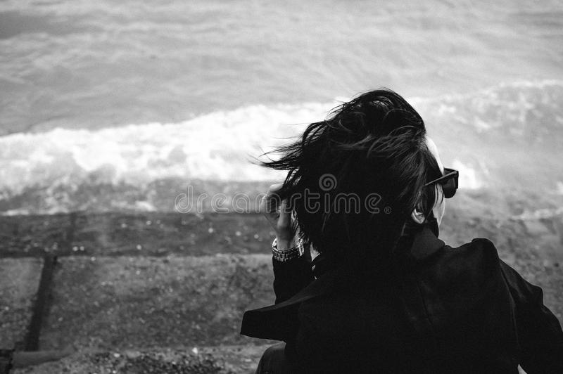 Fashionable portrait of a young brunette woman in black clothes, jeans T-shirt, coat and sunglasses, in a Gothic style sad mood. o. N an empty beach, on an royalty free stock photo