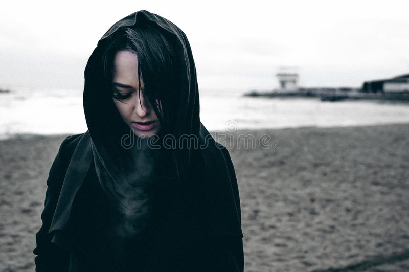 Fashionable portrait of a young brunette woman in black clothes, jeans T-shirt, coat and sunglasses, in a Gothic style sad mood. o. N an empty beach, on an stock photography