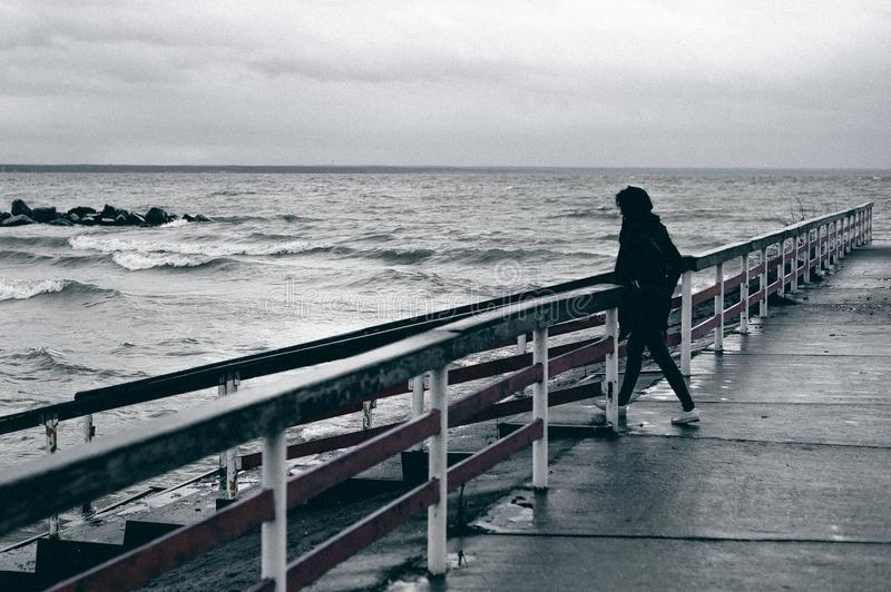 Fashionable portrait of a young brunette woman in black clothes, jeans T-shirt, coat and sunglasses, in a Gothic style sad mood. o. N an empty beach, on an royalty free stock photos