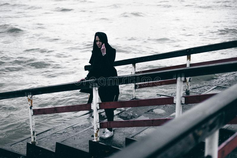 Fashionable portrait of a young brunette woman in black clothes, jeans T-shirt, coat and sunglasses, in a Gothic style sad mood. o. N an empty beach, on an royalty free stock photography