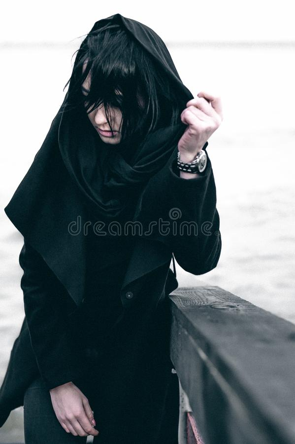 Fashionable portrait of a young brunette woman in black clothes, jeans T-shirt, coat and sunglasses, in a Gothic style sad mood. o. Emotional fashionable stock photo