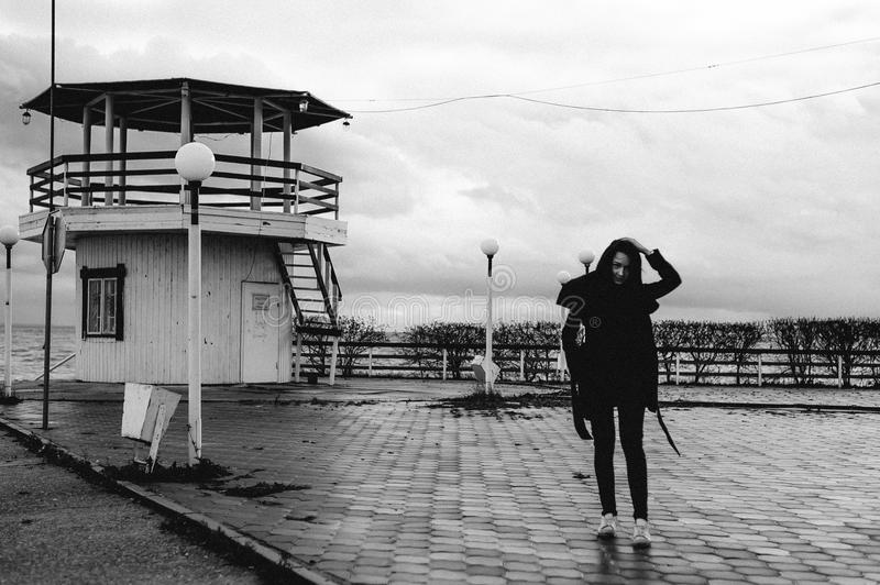 Fashionable portrait of a young brunette woman in black clothes, jeans T-shirt, coat and sunglasses, in a Gothic style sad mood. o. N an empty beach, on an stock images