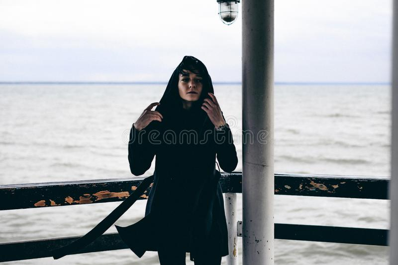 Fashionable portrait of a young brunette woman in black clothes, jeans T-shirt, coat and sunglasses, in a Gothic style sad mood. o. N an empty beach, on an royalty free stock images