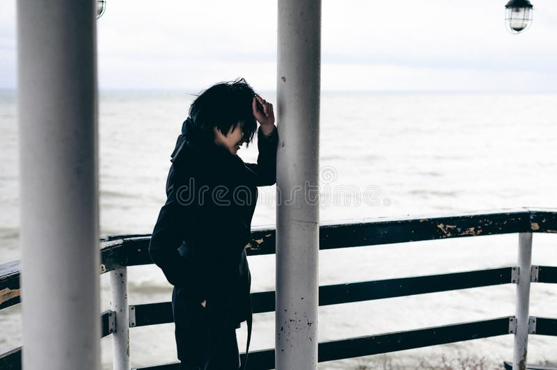 Fashionable portrait of a young brunette woman in black clothes, jeans T-shirt, coat and sunglasses, in a Gothic style sad mood. o. N an empty beach, on an stock photo