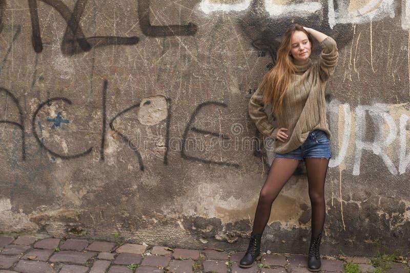 Fashionable pretty girl posing near a stone wall. stock photo