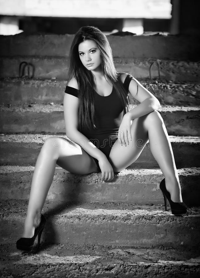 Fashionable pretty young woman with long legs sitting on old stone stairs. Beautiful long hair brunette on high heels shoes posing royalty free stock photos
