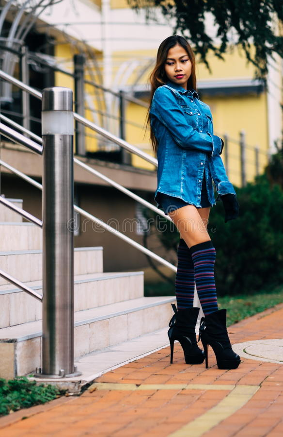 Fashionable pretty young woman wearing blue jeans, and long striped knee socks royalty free stock photography