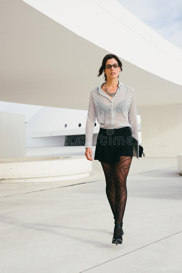 Fashionable professional woman walking outside stock image