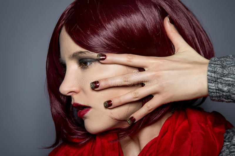 Fashionable Red Nail Polish. Woman with red hair and scarf showing nail polish art or manicure design stock images