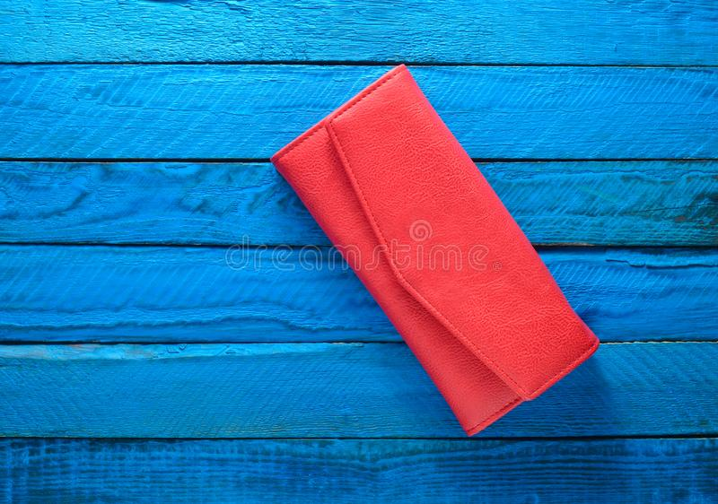 Fashionable red purse on a blue wooden background. Top view. Trend of minimalism. stock photography