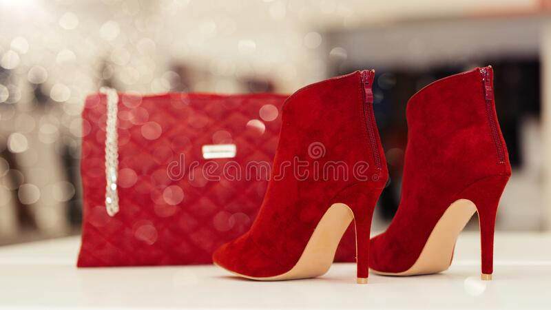 Fashionable Red Women Leather Shoes with high heels and purse on the shelf at the shoe store. Shopping and discount concept royalty free stock photo