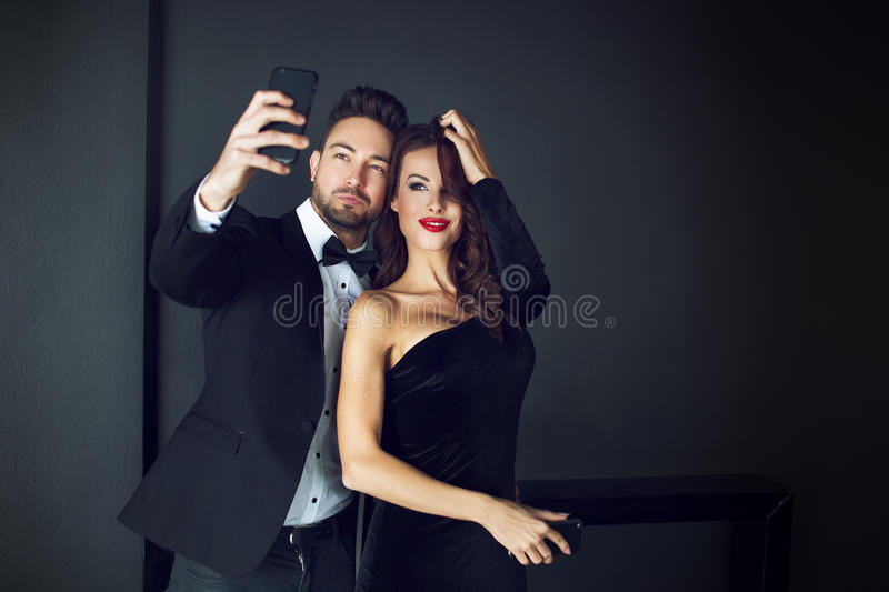 Fashionable rich celebrity couple taking selfie. Indoor stock images